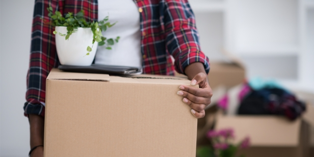A Black woman in flannel holding a box with a small plant on top of it. Half-packed boxes are in the background because she is in the process of moving.