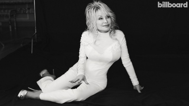 The black and white billboard magazine cover of Dolly Parton has her sitting against a black background in a white catsuit