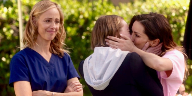Station 19's captain Maya Bishop and Grey's Anatomy's Dr. Carina DeLuca share a make out in the sunshine as Grey's Anatomy recent resident bisexual, Dr. Teddy Altman, looks on proudly.