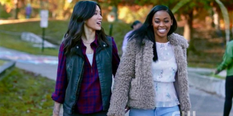 """Grace Choi and Anissa Pierce from """"Black Lightning"""" hold hands and smile on a fall date in the park."""