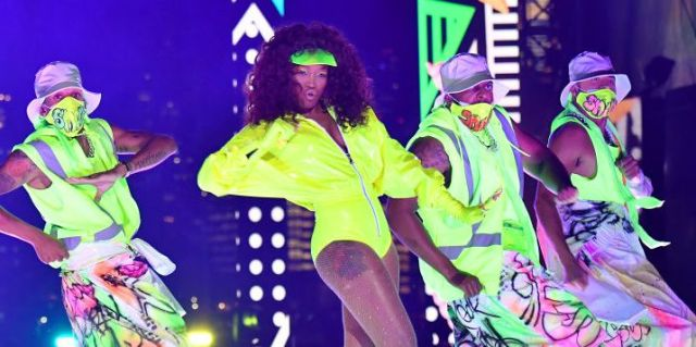 Keke Palmer performing on stage during this years MTV Video Music Awards. She is in a neon yellow leotard dancing with dancers in neon green masks and matching pants.