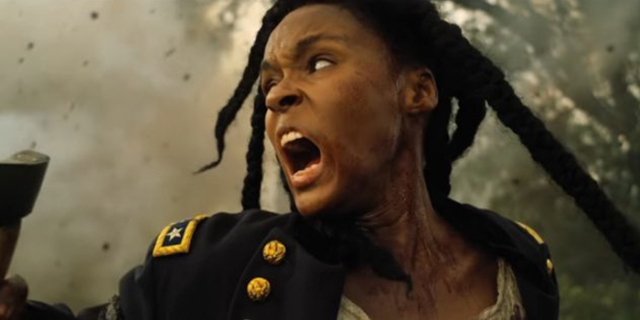 "Janelle Monáe in ""Antebellum"" as the character Eden. Eden screams in anger, her face in profile to the camera, as smoke from torches fill the screen behind her."