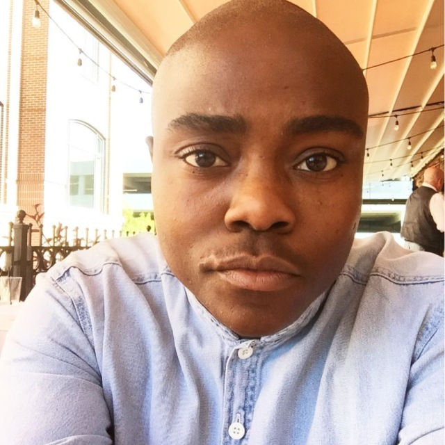 a photo of the author from the shoulders up, he's wearing a light blue button-up shirt, buttoned to the top. he is Black and bald with thick eyebrows, big brown eyes, and he looks into the camera with a slight bemusement and lift of the left side of the lip.