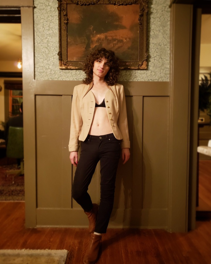 Drew is leaning up against a wall, with one foot propped up against the wall behind her; she's wearing black skinny jeans and ankle boots with a an open blazer worn over a black bra.