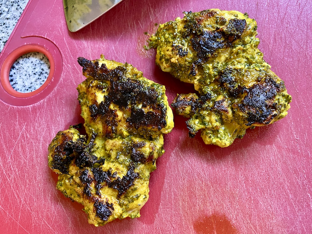 a red cutting board with two yellow-tinted chicken thighs with a browning on the outside