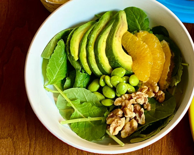 a shallow wide bowl with a bed of kale and fanned slices of avocado on top, slices of oranges nestled against those, a small pile of green edamame, and a small pile of walnuts