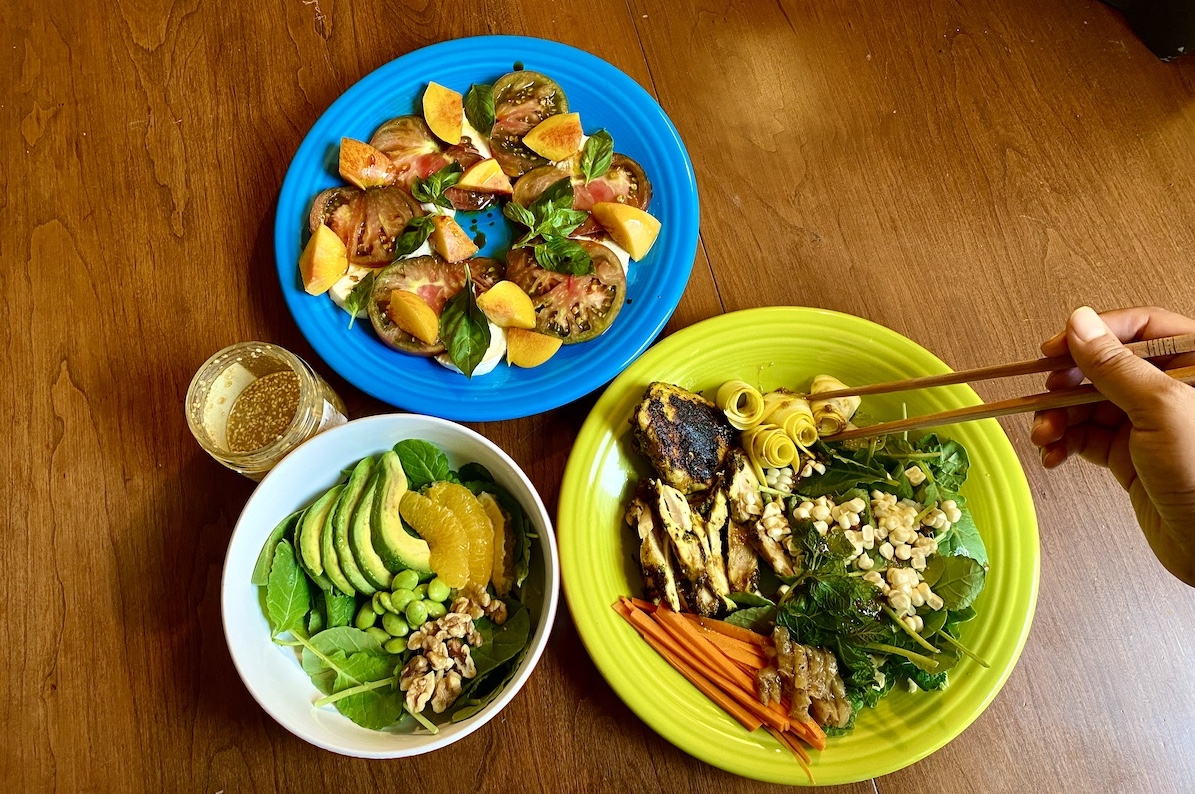 three salads on a table: one with avocado and orange in a small bowl in the bottom left ocrner, one on a bright blue plate with tomatoes , mozzarella and basil, and one on a bright green plate with chicken, carrots, corn kernals on top of a bed of greens