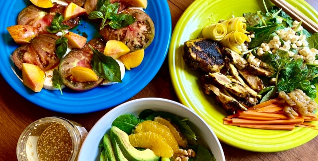three dishes sit on a table touching their edges. a bowl with a peek of avocado and orange is at the bottom, a blue plate with tomatoes and nectarines is on the top right, and a bright green plate with chicken, corn, carrots and greens, and small rolls of yellow squash.