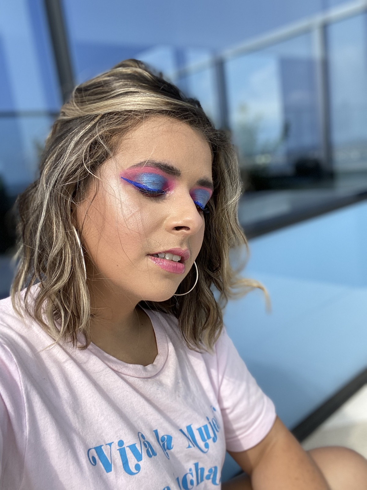 The author, Olivia Zayas Ryan, poses with a full face of makeup. Her eyes are closed and the makeup is dramatic, blue and pink. She wears large hoop earrings and looks at peace.