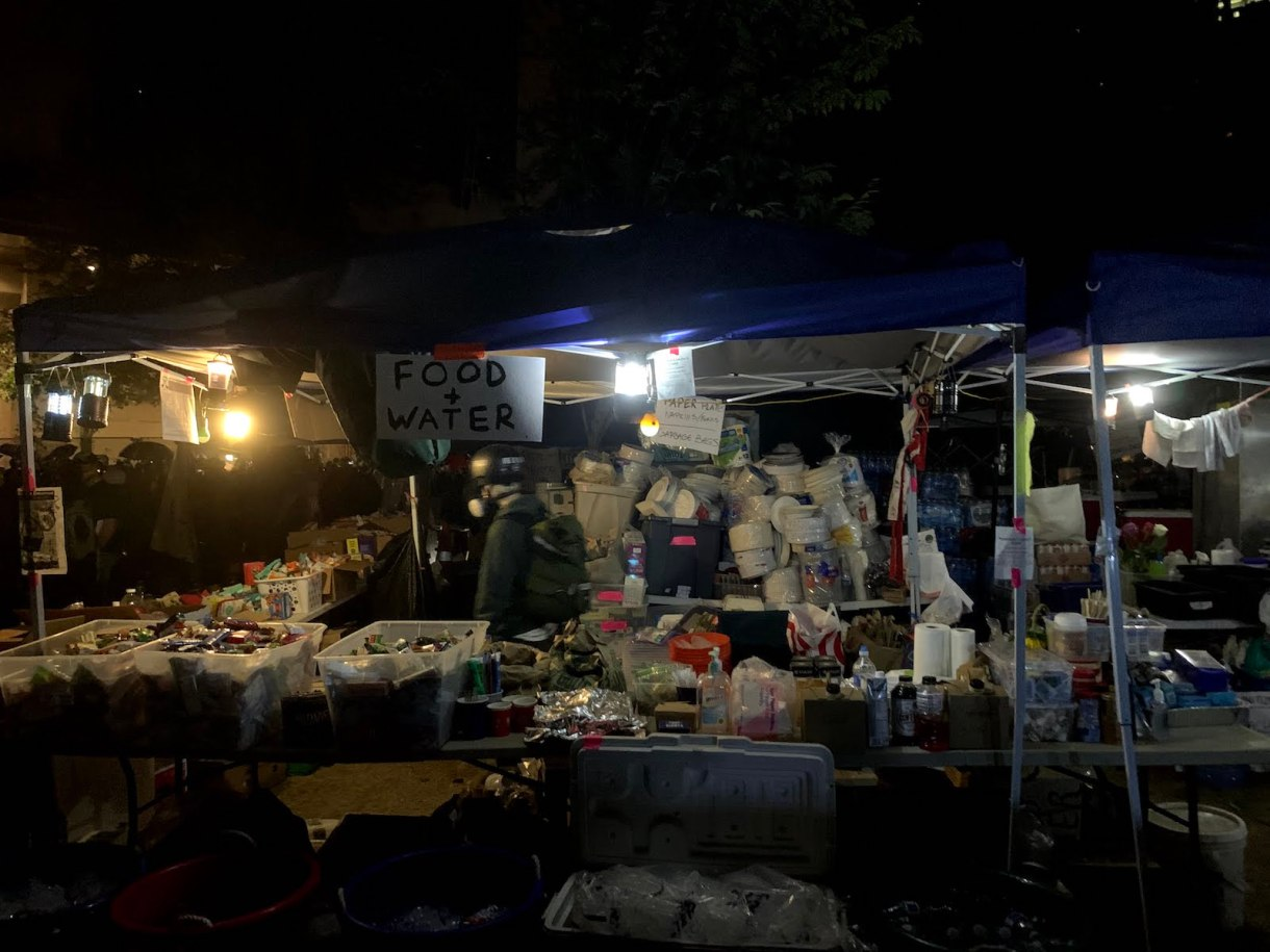 A mountain of donated food, water, and other supplies at Riot Ribs, a free, volunteer-run outdoor kitchen that fed protesters and community members throughout July.