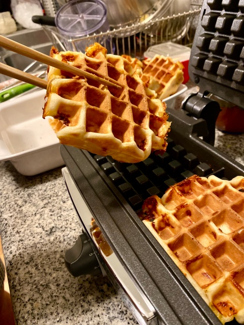 cripsy waffles being pulled hot out of a waffle iron with chopsticks