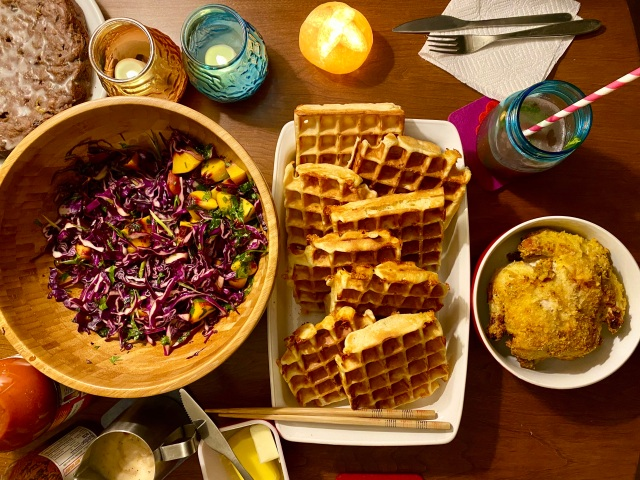 an overhead view of a table setting with a large bowl of purple cabbage salad, a tray of waffles, a pitcher of gravy, a small bowl with a little round fried hen nestled inside