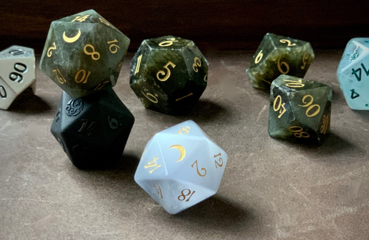 A composed photo of a beautiful set of Dungeons & Dragons dice, in a range of colors and materials from deep green cloudy gemstone with gold lettering to opaque matte black to cloudy quartzlike white to silver metal.