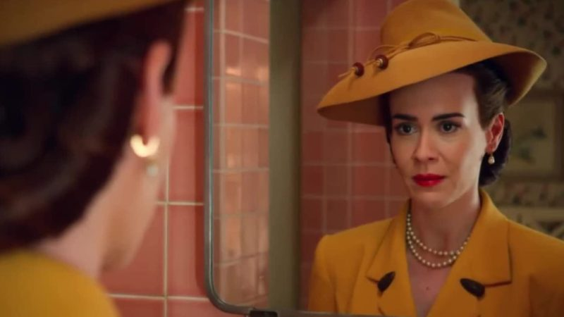 Sarah Paulson as Nurse Ratched in Ratched (showrunner Ryan Murphy, 2020). She is in a mustard yellow hat and dress styled like the 1940s and looks at herself in the mirror in a pink bathroom.