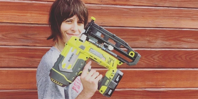 Kate Moennig stands in front of a wood panel wall with a very large power tool of some sort that's bigger than her own head!