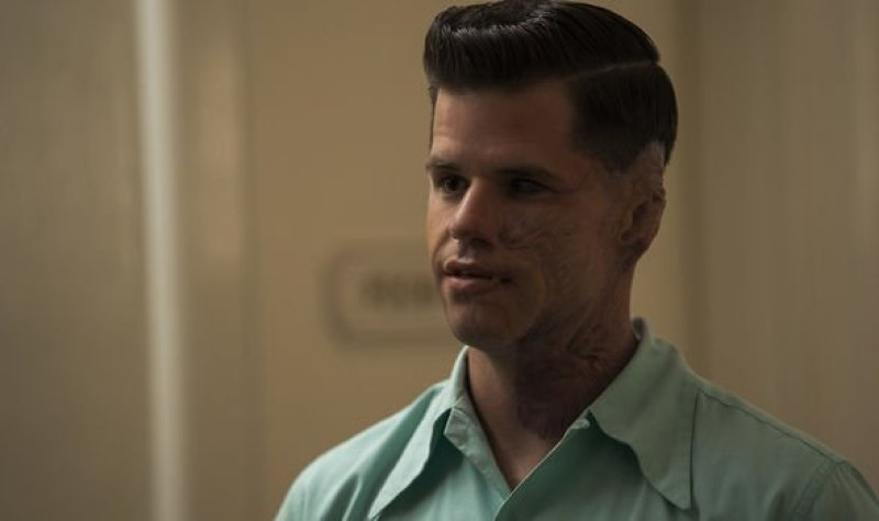 "Charlie Carver as Huck in the Netflix show ""Ratched."" He stares off to the left in a light blue colored shirt and has brunette hair in a close cut style of the 1940s."