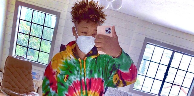 Samira Wiley poses for a selfie in her mirror with a mask on. She is wearing a tie dye sweatshirt and growing out her signature haircut.