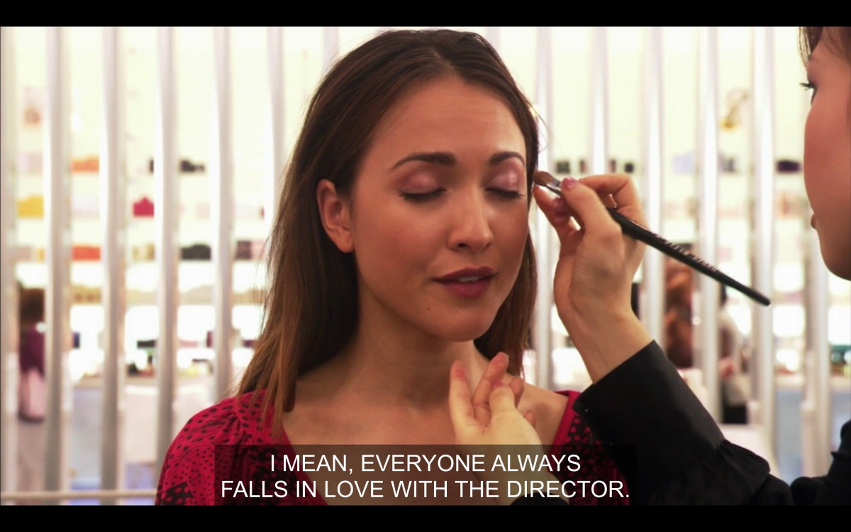 """A makeup artist (not in the shot) does Adele's makeup while Adele says """"I mean, everybody always falls in love with the director"""""""