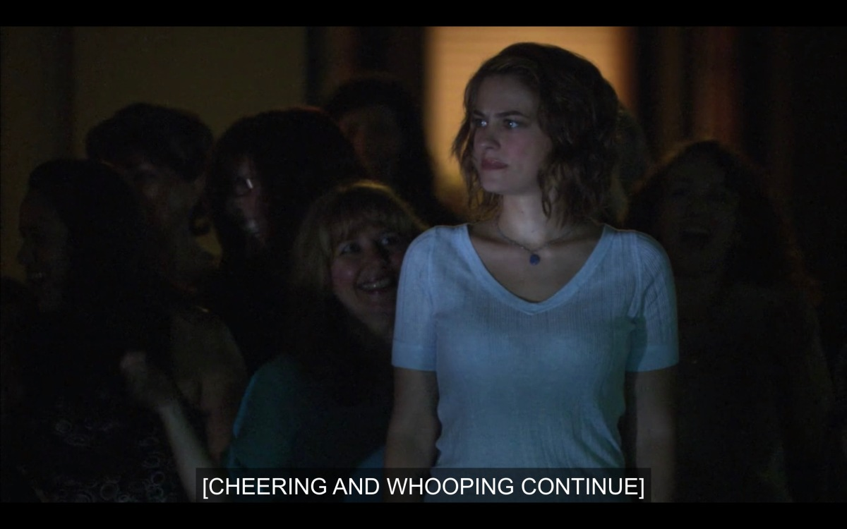 """Molly is confused, standing at her mother's party in a white v-neck not sure what's going on. The caption reads """"Cheering and whooping continue"""""""
