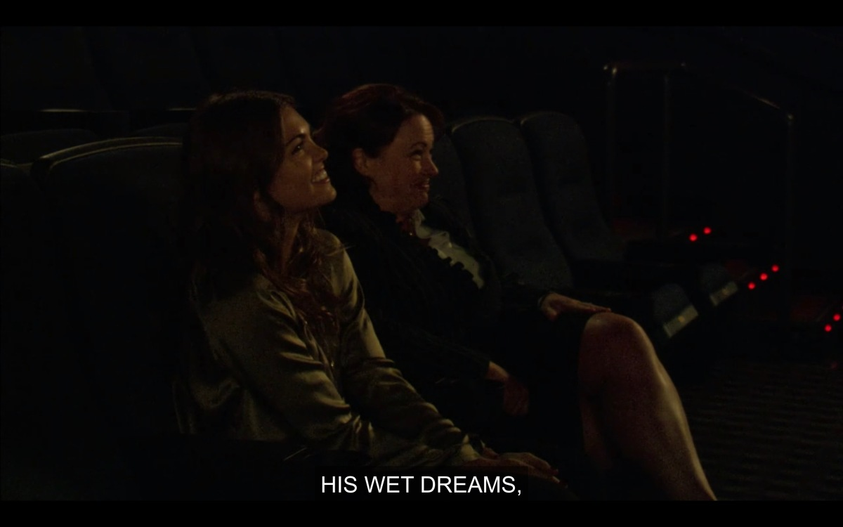 "Niki sits in the movie theater watching ""Liquid Heat"" next to her agent while an off-screen agent says ""in his wet dreams"""