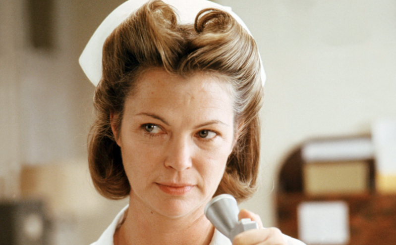 American actress Louise Fletcher as Nurse Ratched in 'One Flew Over The Cuckoo's Nest', directed by Milos Forman, 1975. She stares off to the right of the camera while speaking into a microphone.
