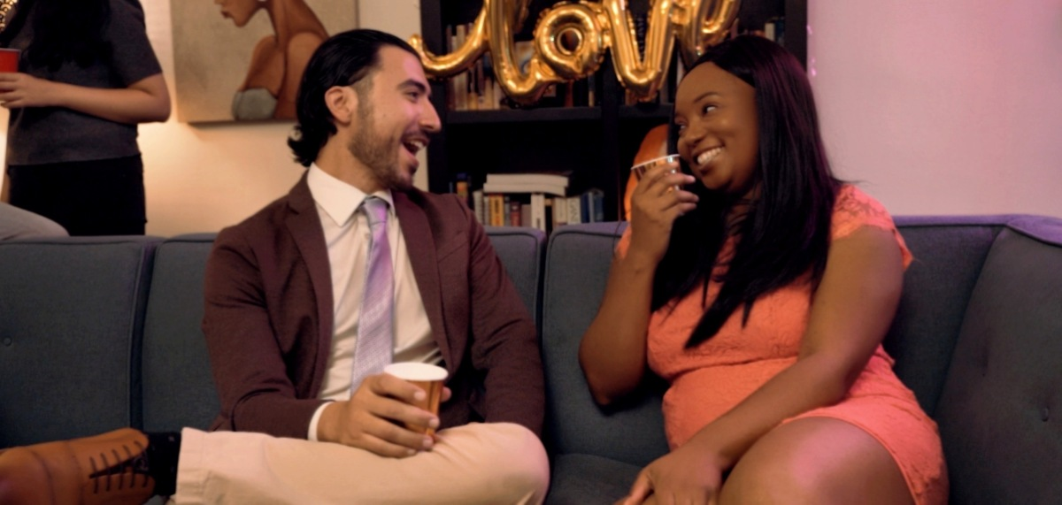 Two people sit on a navy blue couch in a party setting; on the left, a light-skinned man with longer hair and a short beard is laughing, wearing a formal jacket and a tie and holding a Solo cup. On the right, a Black woman with long straight hair and a light pink dress is making eye contact with him and laughing as she lifts a cup to her mouth.