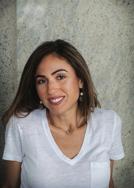a Palestinian American woman in a white v-neck t-shirt stands in front of a wall with a half smile, her face turned just slightly away from the camera. she has light brown, straight shoulder length hair, dark eyebrows and a red lipstick smile