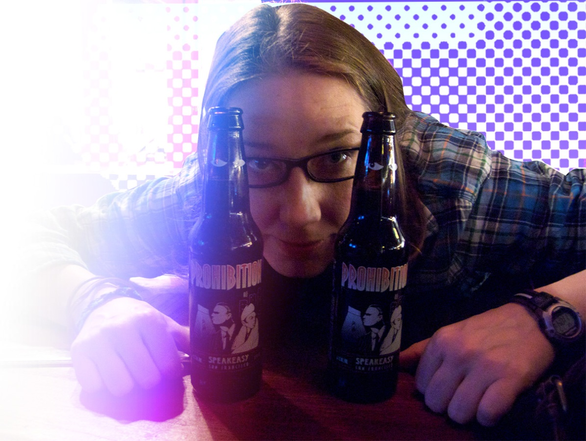 An up-close photo of Heather seated, peering at the camera from between two beer bottles on a table; she's wearing a blue flannel shirt and glasses.