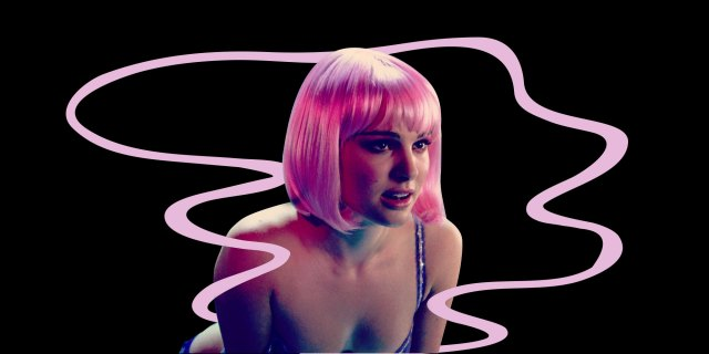 A woman in a pink wig, leaning forward against a black background with a pink graphic element winding through