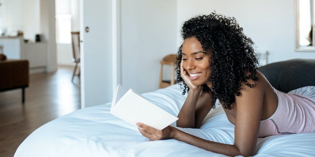 a Black woman reading a book on top of the covers of a bed