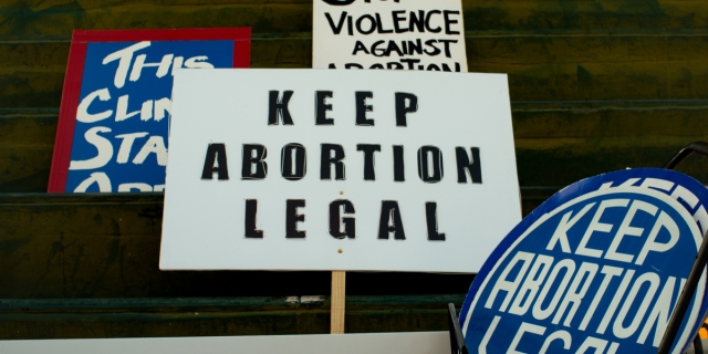 A range of pro-choice protest signs, the central one reading KEEP ABORTION LEGAL
