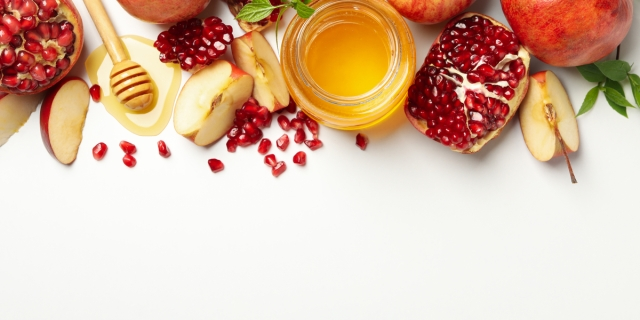 Rosh Hashanah theme on a white background including apples, honey, and pomegranates to symbolize the Jewish New Year