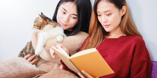 two women reading from the same book, with a cat