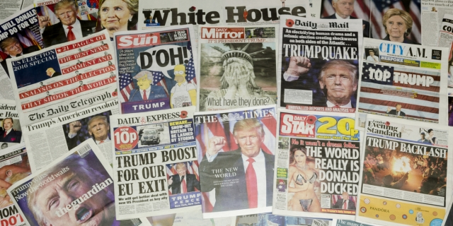 A zoomed-out photo of dozens of world newspapers featuring Trump-related headlines laid out on a surface.