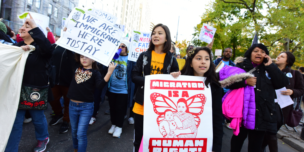 """A pro-migrant protest or rally, with multiple people marching and holding signs; two visible ones read """"Migration is a human right"""" and """"we are immigrants here to stay."""""""