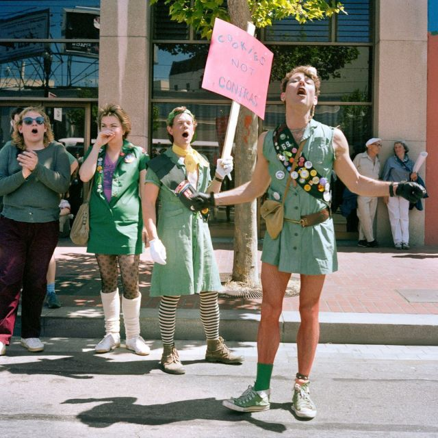 """Adult queers wear Girl Scout uniforms in 1986 during a protest. In the background, one of the Girl Scout-clad protestors holds a sign that says """"Cookies not Contras"""" in the trans pride colors."""