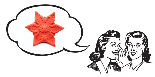 A black and white illustration of two white women in 50's garb whispering to each other; above their heads, a speech bubble contains an image of a bright orange star-shaped silicone vibrator.