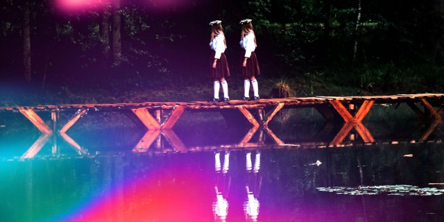 two girls in school uniforms walking across a bridge over the water in a forest