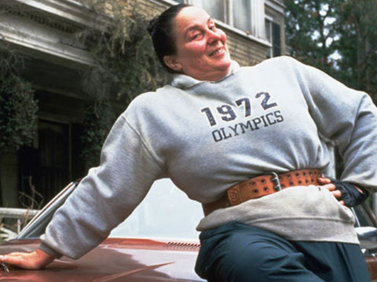 Miss Trunchbull from the Matilda movies leans back across the hood of a car, wearing a gray sweatshirt that reads 1972 OLYMPICS, a weightlifting belt and gloves