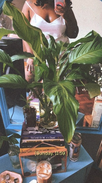 Shelli in a mirror surrounded by books, plants and coffee