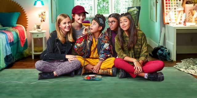 The cast of Netflix's The Baby-Sitters Club sit together on the floor a green bedroom. Claudia is in the center of the group, and she talks on a clear phone from the 1990s.