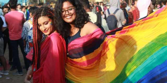 Two South Asian queer femmes with long hair embrace underneath a rainbow flag.