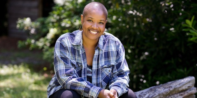 A photo of Angela Walker, a Black woman with a shaved head, seated on a log, leaning forward and smiling broadly in a blue checked flannel shirt