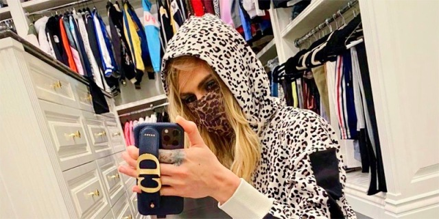Cara Delevingne takes a selfie in her oversized closet. She's wearing a leopard print hoodie with a leopard print mask.