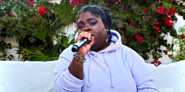 The rapper/singer Chika is in a purple sweatshirt, sitting on a couch, and singing you a love song into a microphone. The roses behind her only further up the romance.