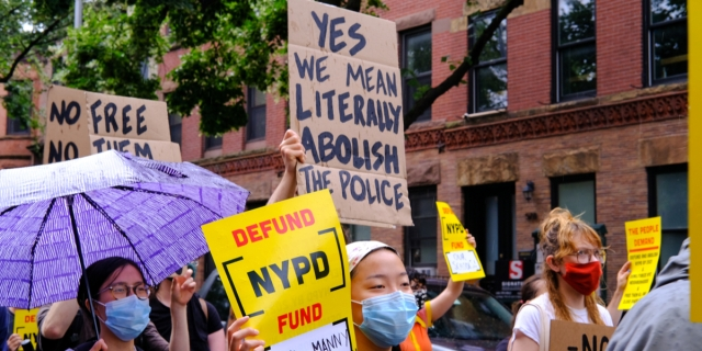 "a group of protestors in masks, one of them holds a sign that says ""yes we literally mean abolish the police"" and another says ""defund NYPD"""