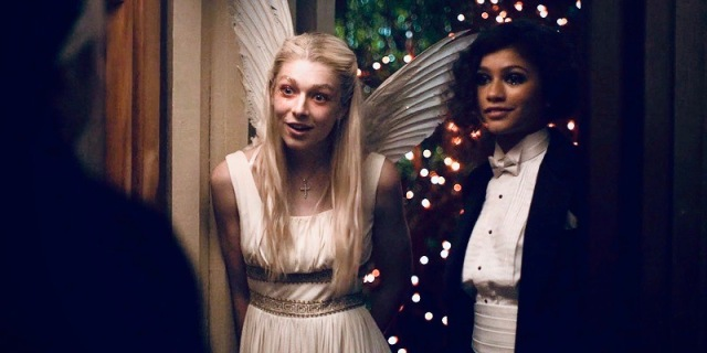 """A photo still of the television series """"Euphoria"""" in which Rue and Jules are dressed up as Romeo & Juliet. The lights sparkle behind them."""