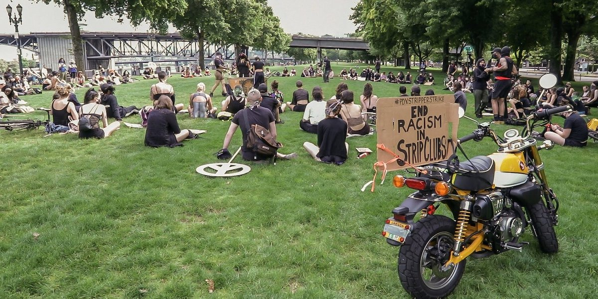 """a group of people gathered on a lawn in portland, wearing masks and watching a few speakers in the middle. there is a sign taped to a motorcycle in the foreground that says """"#pdxstripperstrike End Racism In Strip Clubs"""""""
