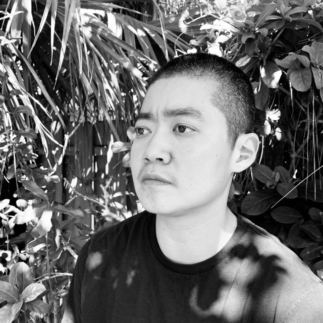 black and white photo of patty yumi cottrell, a trans korean adoptee, looking somberly into the distance. they have close-cropped hair and are wearing a black t-shirt as they stand in front of a thicket of palms leaves.