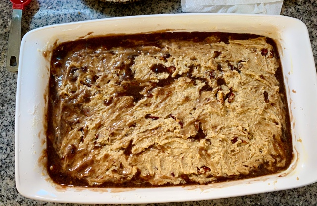 a full casserole pan with a pale blondie batter on top, and a darker layer of browned butter seeping up from beneath